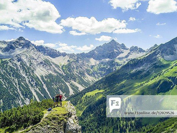 Drei Wanderer in den Bergen  Ausblick auf den Hochvogel  Allgäu  Allgäuer Hochalpen  Bayern  Deutschland  Europa