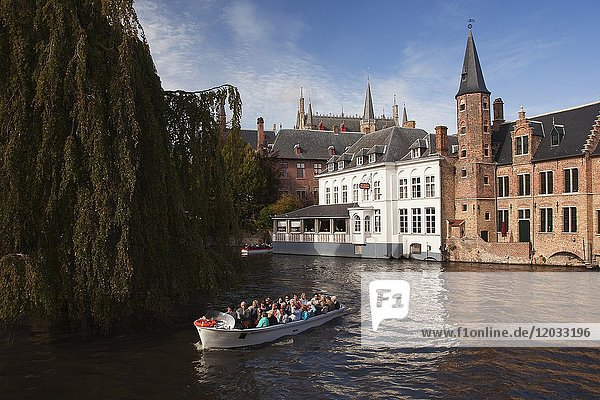 Tourists on the boat during a trip near the Rozenhoedkaai  Canal and Tower  Bruges  West Flanders  Belgium  Europe.
