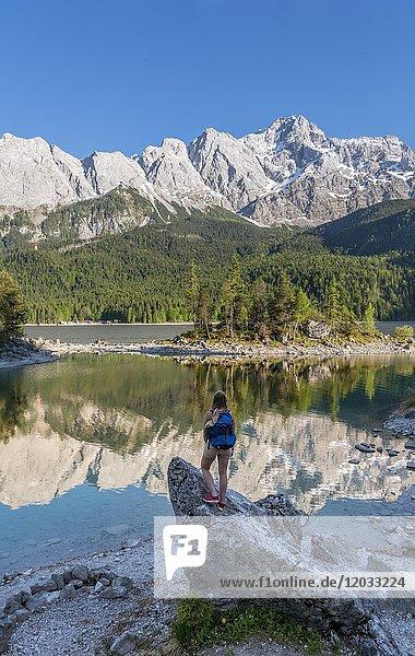 Wanderin steht auf Felsen  Blick in die Ferne  Eibsee und Zugspitze  Wettersteingebirge  bei Grainau  Oberbayern  Bayern  Deutschland  Europa