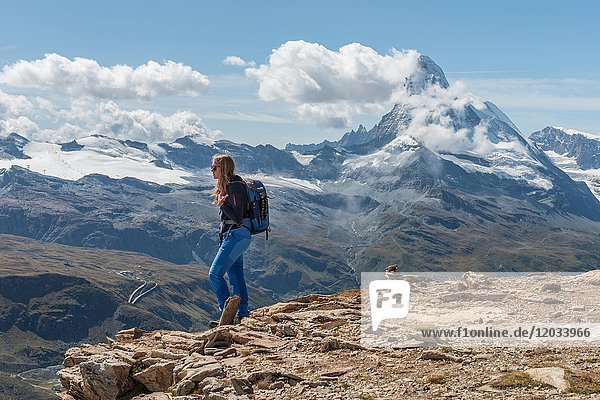 Wanderin steht auf Felsen  hinten schneebedecktes Matterhorn  Wallis  Schweiz  Europa