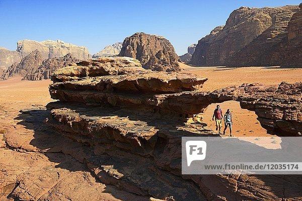 Couple hiking at Rock Arch  Al Borg Alsagheer  Wadi Rum  Jordan  Asia