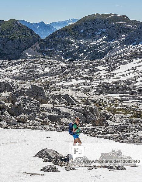 Wanderinn auf dem Wanderweg zum Königssee und der Wasseralm  Steinernes Meer mit Schnee im Frühling  Nationalpark Berchtesgaden  Bayern  Deutschland  Europa