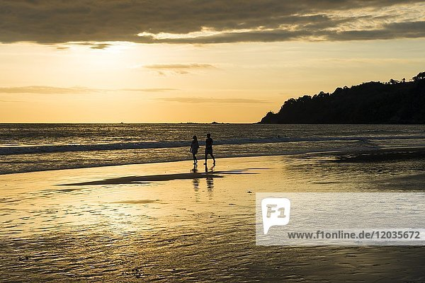 Paar  Mann und Frau  Spaziergang am Strand  Sonnenuntergang  Playa Espadilla  Nationalpark Manuel Antonio  Costa Rica  Mittelamerika