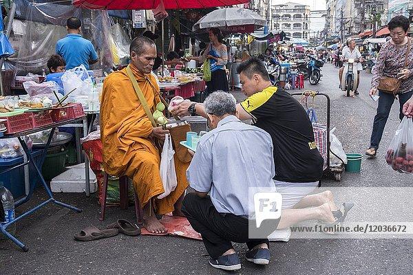 Alms giving at Nora street market  Hatyai  Thailand
