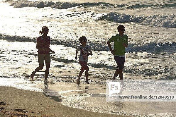 Familie joggt am Sandstrand  Sir Bani Yas Island  Vereinigt Arabische Emirate