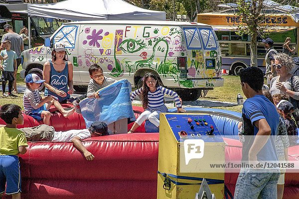 Local children enjoy a ride that imitates surfing at a Costa Mesa  CA  community festival. Note control panel and van in background decorated by local amateur artists.