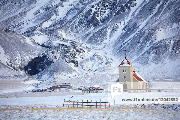 Church and isolated farm against snow covered mountains  winter afternoon on the road to the Snaefellsnes Peninsula  Iceland  Polar Regions