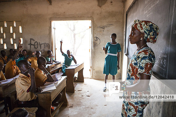 A female teacher teaching at the front of the classroom at a primary school in Ghana  West Africa  Africa