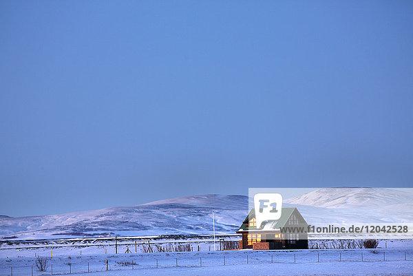 Winter landscape at dusk showing lone cabin bathed in evening sunlight  near Seljalandsfoss  South Iceland  Polar Regions