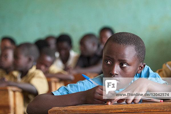 A school girl glances up to read the blackboard  Rwanda  Africa