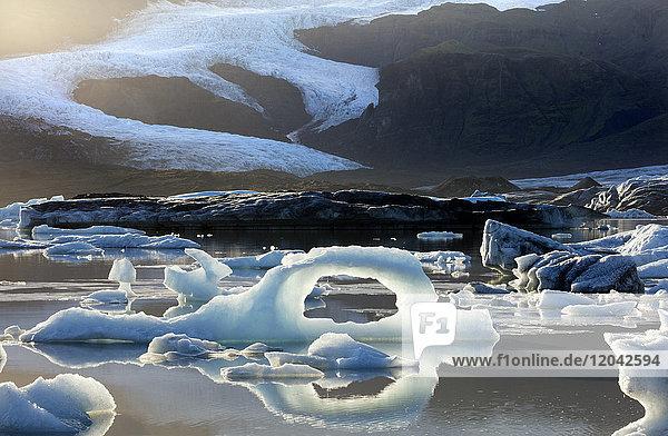 Ice arch among icebergs floating on Fjallsarlon lagoon  near Jokulsarlon  South Iceland  Polar Regions