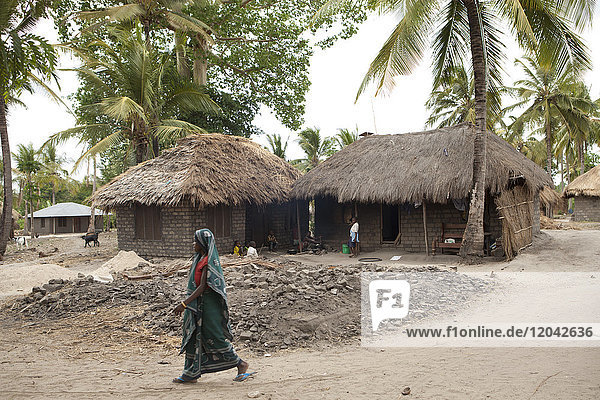A woman walks past a traditional mud hut home with a solar panel on the top of it  Tanzania  East Africa  Africa