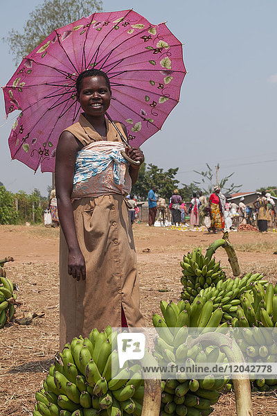 A lady selling bananas at the market shelters from the sun under a pink umbrella  Rwanda  Africa