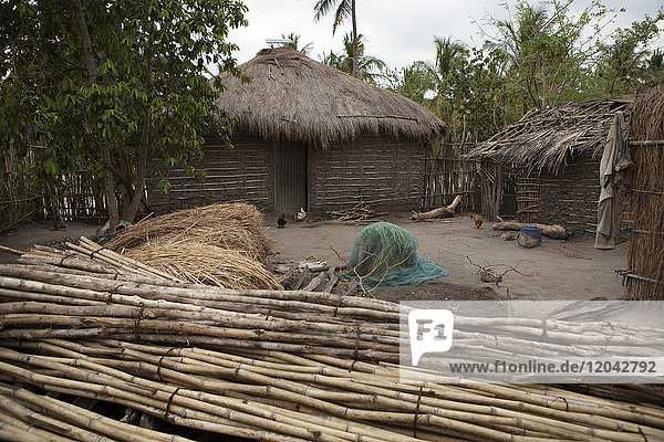 A traditional mud hut home with a thatched roof and a solar panel on the top of it  Tanzania  East Africa  Africa