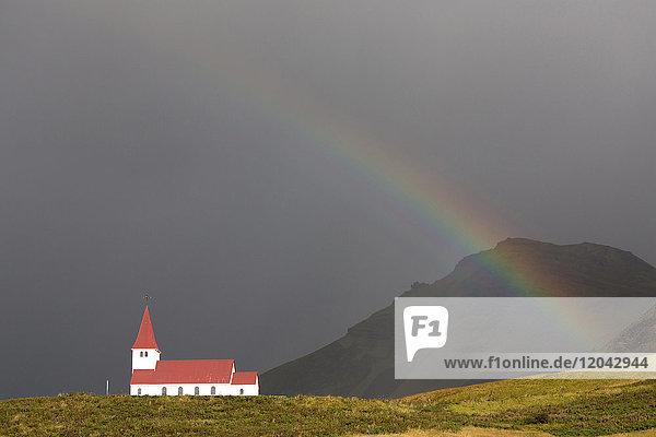 Church and rainbow against stormy sky and mountains  Vik Y Myrdal  South Iceland  Polar Regions