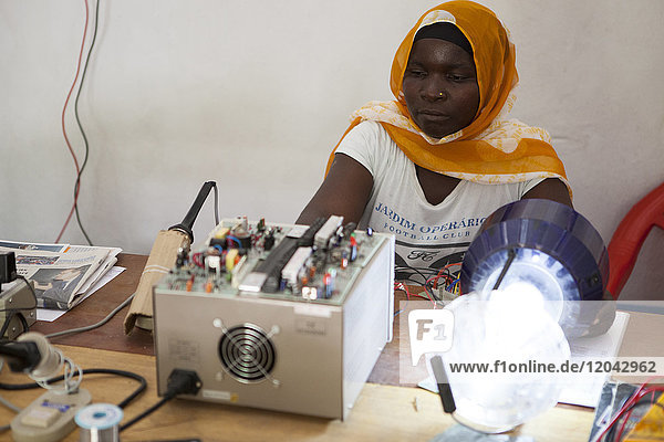 A female solar engineer  known as a solar mama  using a soldering iron to fix the printed circuit board of a solar lamp  Tanzania  East Africa  Africa