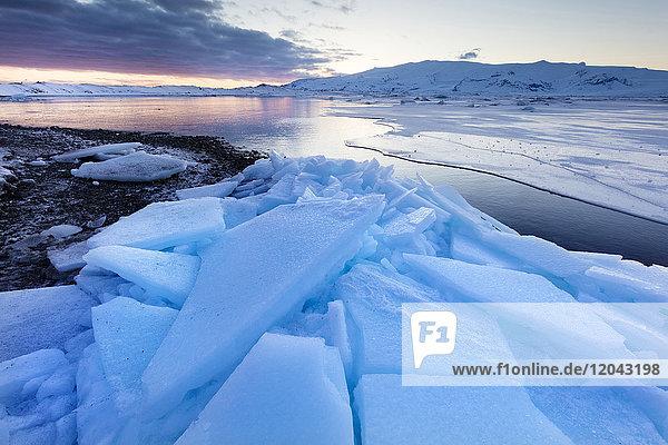 Sunset over frozen Jokulsarlon Glacial Lagoon in winter  South Iceland  Polar Regions