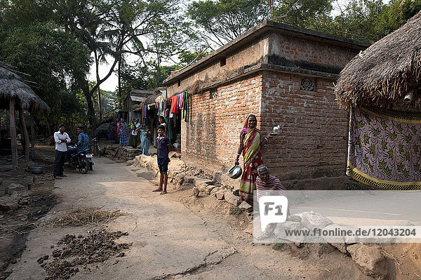 Villagers in typical rural village afternoon scene in the street outside a modern laterite brick built village house  Odisha  India  Asia