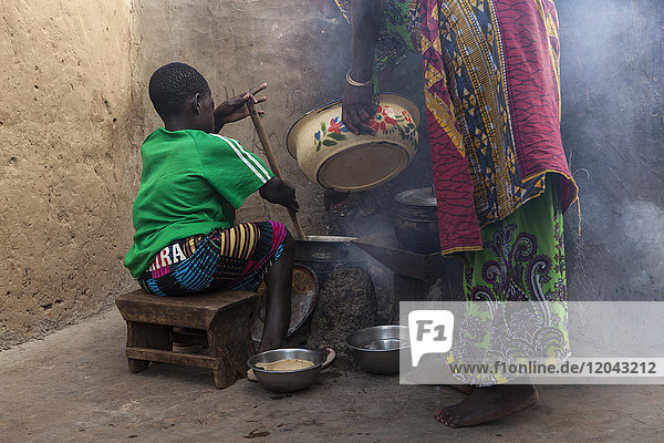 A young girl helping her mother cook at their home in Tinguri  Ghana  West Africa  Africa