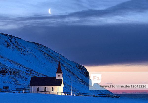 Floodlit church at dawn against snow covered mountains  winter  near Vik  South Iceland  Polar Regions