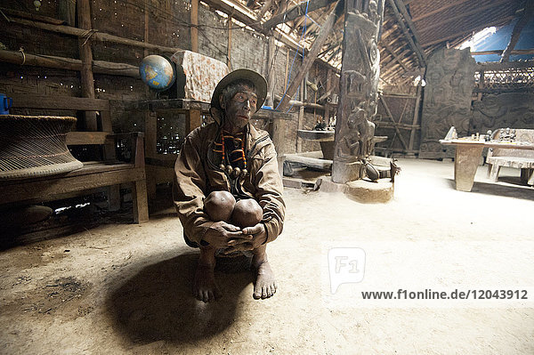 Naga man  Longsha Wangnao  head hunter  with tattooed face and Naga necklace  sitting in communal Naga tribal house  Longwa  Nagaland  India  Asia