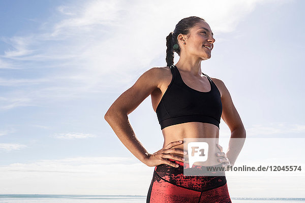 Young female runner on beach with hands on hips against blue sky