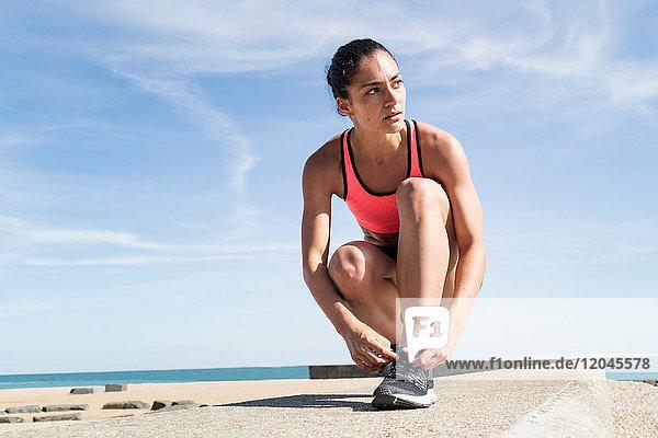 Junge Frau auf Seewall  Schnürsenkel bindend