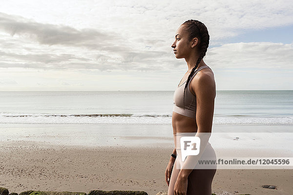 Junge Läuferin blickt vom Strand aus
