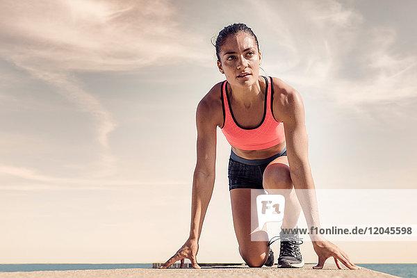 Junge Frau auf Seedeich  in Startposition  bereitet sich auf Lauf vor