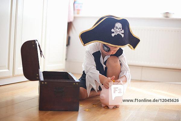 Als Pirat verkleideter Junge legt Geld ins Sparschwein