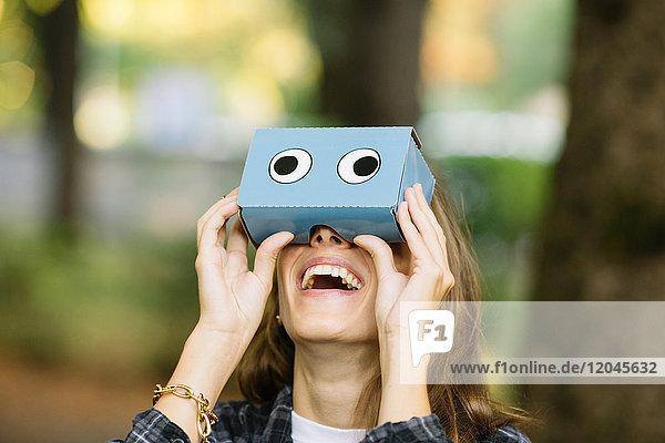 Junge Frau schaut im Park durch ein Pappfernglas auf