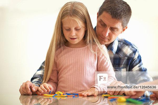 Vater  Sohn und Tochter  am Tisch sitzend  spielen mit Modelliermasse