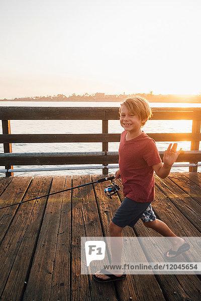 Junge am Pier mit Angelrute winkt lächelnd in die Kamera  Goleta  Kalifornien  Vereinigte Staaten  Nordamerika