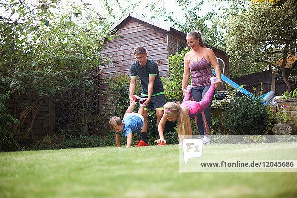 Familie im Garten  mit Schubkarrenrennen
