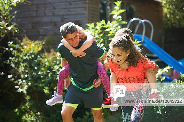 Familie spielt Huckepack-Rennen im Garten