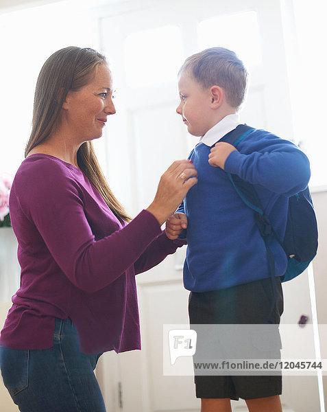 Frau beim Anpassen des Schulpullovers des Sohnes im Flur