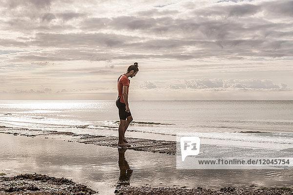 Mann am Ufer mit Blick auf das Meer