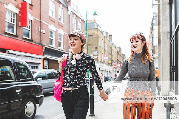 Zwei junge Frauen im Retro-Stil schlendern auf der Straße und halten sich an den Händen