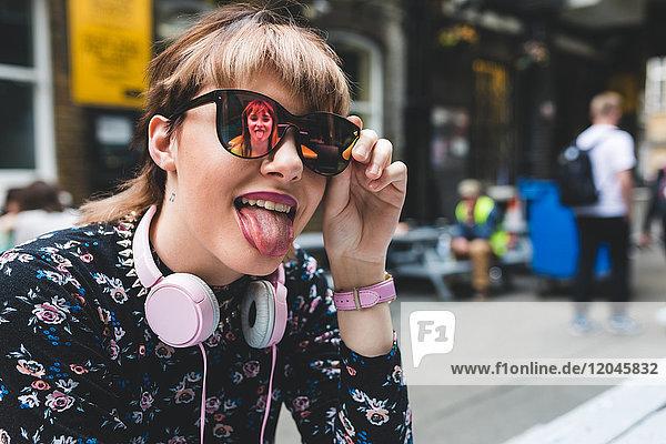 Junge Frau in der Stadt mit Sonnenbrille  die ihre Zunge herausstreckt