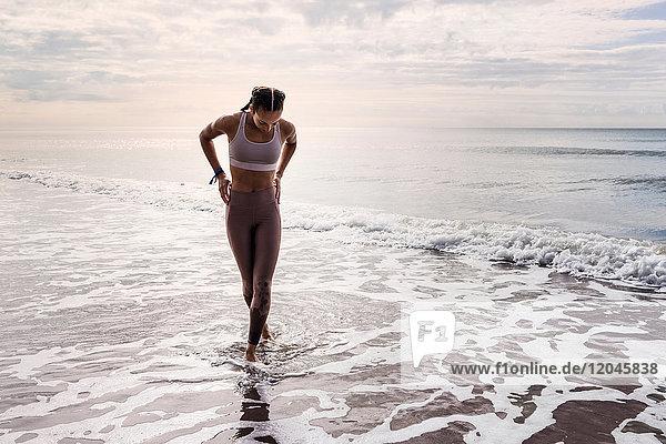 Young woman walking in sea