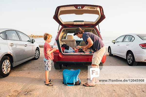 Father and son taking fishing rods from car boot  Goleta  California  United States  North America