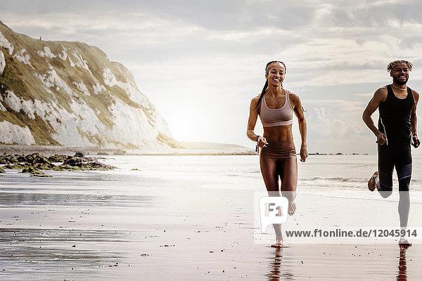 Junge männliche und weibliche Läufer laufen barfuss am Strand