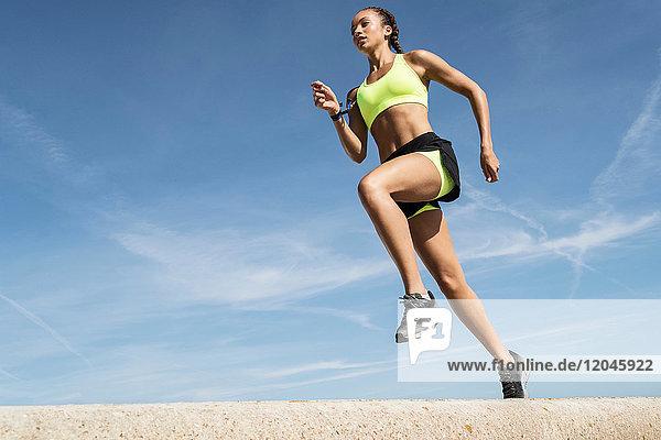 Niedrigwinkelansicht einer jungen Läuferin  die entlang der Seemauer gegen blauen Himmel läuft