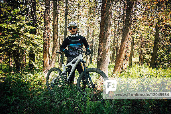 Man in forest with mountain bike  looking at camera  Mammoth Lake  California  USA  North America