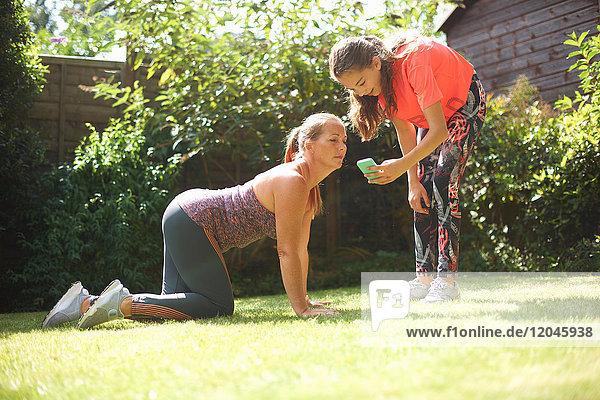 Frau auf Händen und Knien im Garten  schaut auf das Smartphone ihrer Tochter