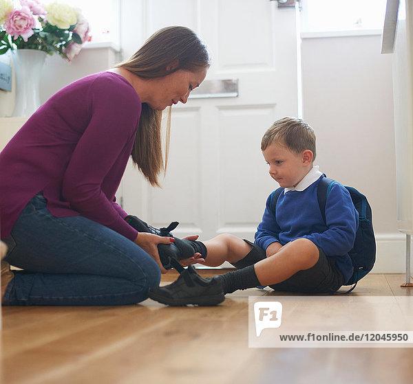 Frau zieht auf dem Flur den Schulschuh ihres Sohnes an
