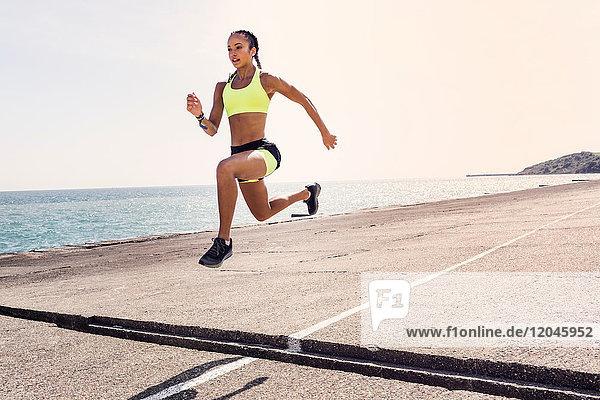 Junge Frau rennt im Freien  springt über die Lücke in der Brücke  mitten in der Luft