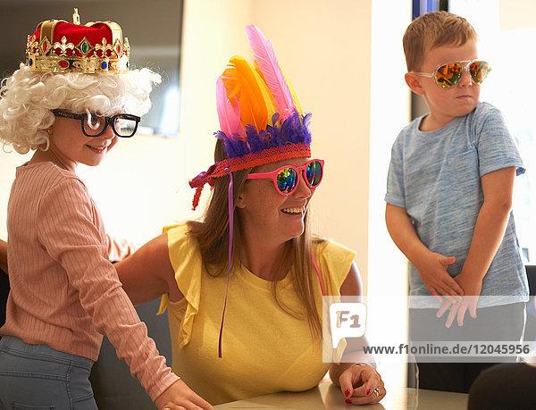 Mutter  Sohn und Tochter spielen Verkleiden  tragen lustige Hüte und Brillen  lachen