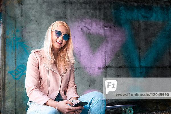 Porträt einer jungen blonden Skateboarderin mit Sonnenbrille im Skateboard-Park