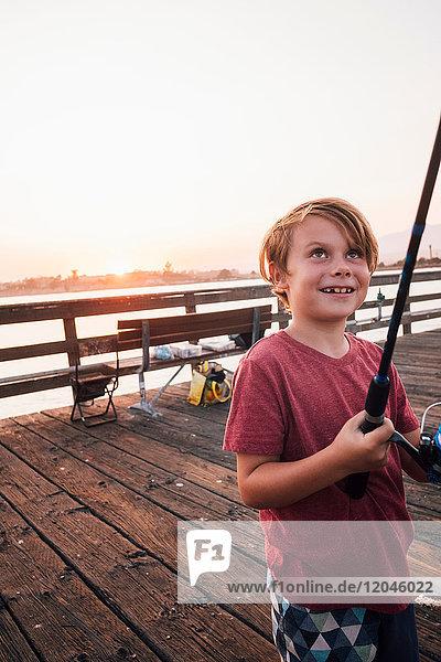 Boy on pier with fishing rod smiling  Goleta  California  United States  North America